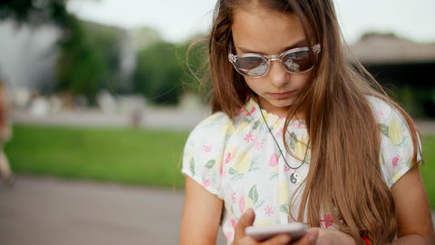 Smiling teen girl surfing internet on mobile phone in summer park Live Action