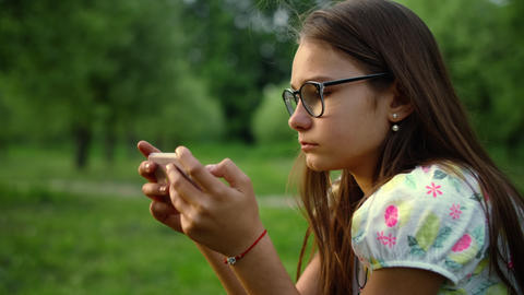 Close up serious girl texting in smartphone in summer park Live Action