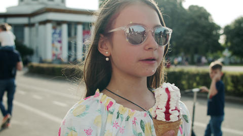 Pretty girl eating ice cream cone. Relaxed teen girl walking in amusement park Live Action