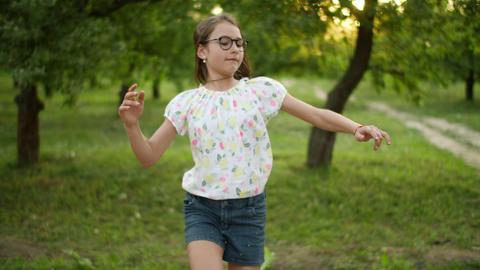 Happy girl making having fun outdoors. Teenage girl dancing outside Live Action