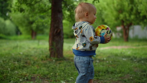 Little boy carrying ball in forest. Closeup smiling toddler boy running outdoors Live Action