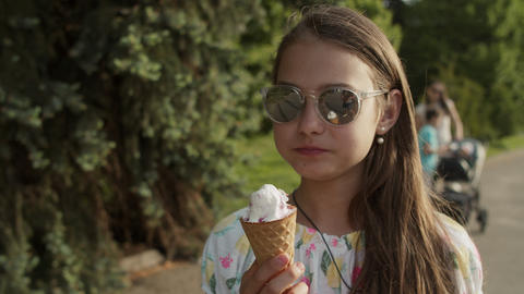 Relaxed teenage girl walking in amusement park. Cute girl eating ice cream Live Action