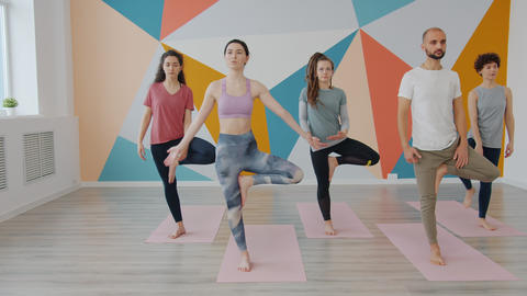Youth students enjoying relaxation in yoga class doing tree position balancing Live Action