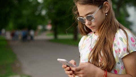 Cheerful girl playing games on phone in park. Playful girl using smartphone Live Action