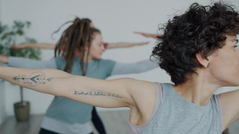 Yoga teacher demonstrating asanas speaking during group class in studio Live Action