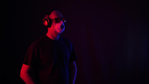 Relaxed male music lover in respirator enjoying music Live Action