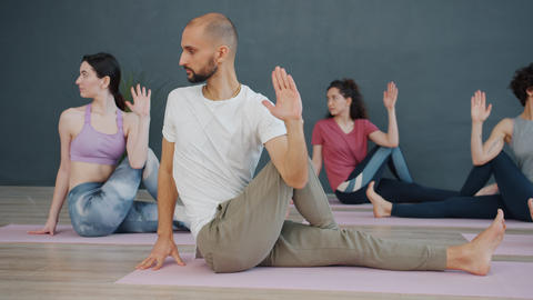 Youth male and female busy with yoga asanas sitting on mats in light studio Live Action