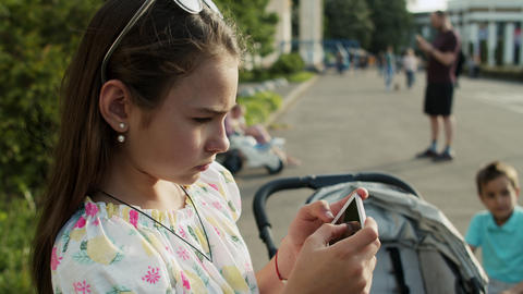 Serious girl playing on mobile phone in park. Cute girl…, Live Action