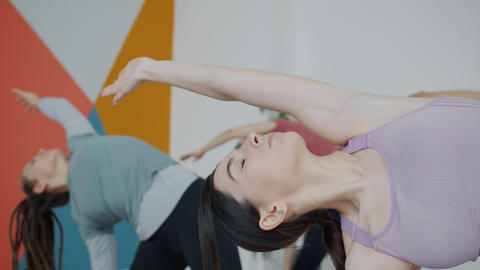 Cute girl in stylish top practising yoga in studio focused on healthy activity Live Action