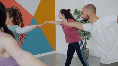 Man and women doing yoga bending stretching arms in studio exercising together Live Action
