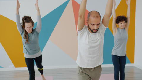 Young attractive man and women doing complex of yoga asanas in modern studio Live Action