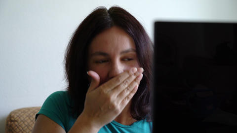 woman sitting befor computer sneezing into hand Live Action