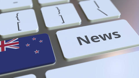 News text and flag of New Zealand on the keys of a computer keyboard. National Live Action
