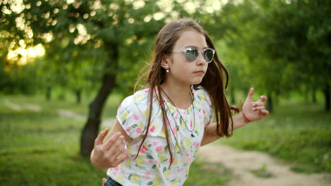 Serious teenage girl dancing outside. Girl making rhythmical movements outdoors Live Action