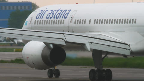 Air Astana Boeing 757 slowing after landing at rainy weather Stock Video Footage