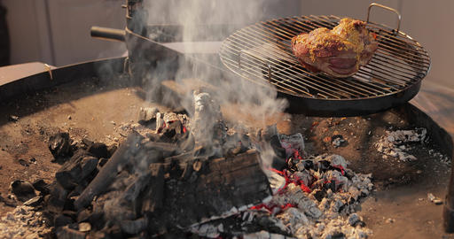 The big piece of the pickled meat lies on a round grill, near big naked flame Live Action