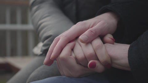 Close-up of Caucasian man's and woman's hands on top of each other. Cheerful Live Action