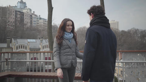Camera approaching to happy loving girl hugging boyfriend outdoors. Portrait of Live Action