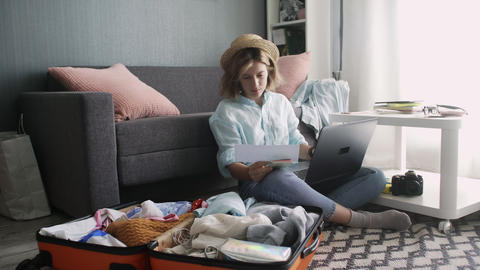 Young girl with laptop, getting ready for road trip and checks vacation tickets Live Action