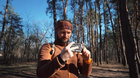 theme tourism hiking forest and technology. Man Caucasian male beard traveler Live Action