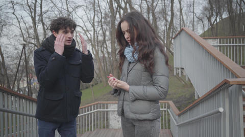 Portrait of brunette Caucasian boy yelling at pretty girl outdoors. Young couple Live Action