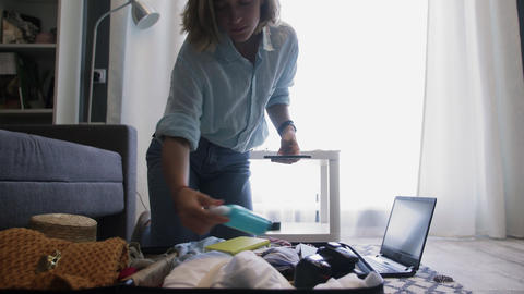 Young woman is hat packing suitcase getting ready for road trip checking list on Live Action