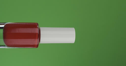 Horizontal rotation of a glass bottle with nail polish, on a green screen. Close ライブ動画