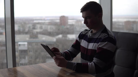 A young man with a tablet sits at a table. A man sits in a cafe by the panoramic Live Action