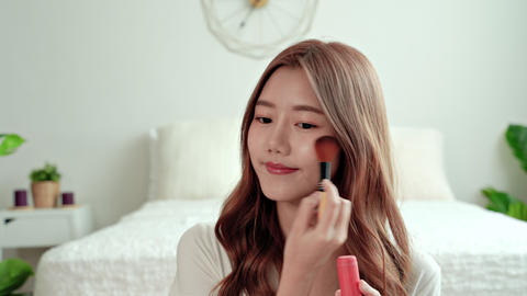 Beautiful woman makes blush on the face using makeup brush sitting in the bedroom. Asian woman makes Live Action