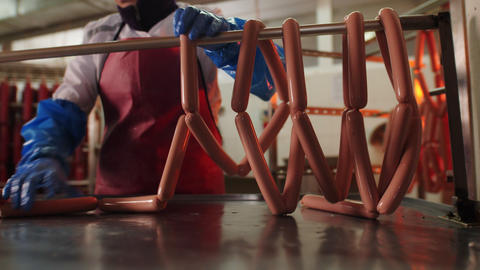 worker puts bar with tasty raw sausages onto rack in shop Live Action