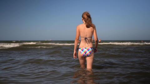 Young happy woman in bikini wading waves in the sea at beautiful beach Live Action