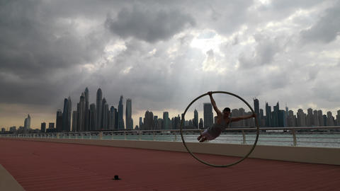 Cyr Wheel artist with cityscape background of Dubai during sunset Live Action