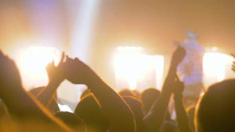 Slow motion: silhouettes of people partying at rock concert in front of stage Live Action