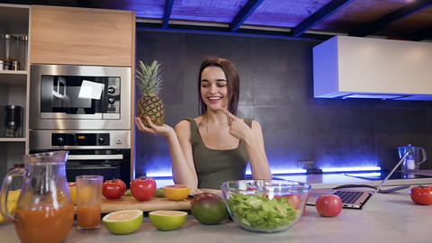 Cheerful contented emotional 25-aged brunette holding pineapple and showing sign Live Action