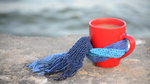 Red mug with coffee tied with blue knitted scarf stands on stone surface Live Action