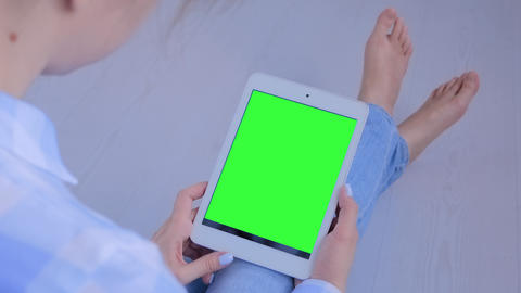 Woman looking at tablet computer with blank green screen - copyspace concept Live Action