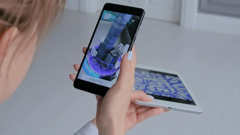 Woman using smartphone and tablet with AR app - 3d model of modern building Live Action