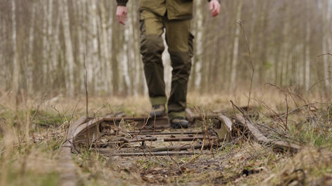 Young man walks along the railway rails in autumn forest Live Action
