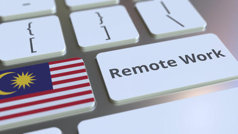 Remote Work text and flag of Malaysia on the computer keyboard. Telecommuting or Live Action
