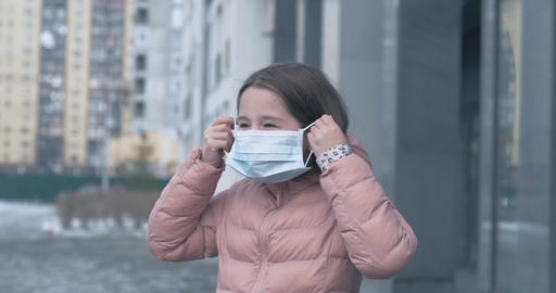 Coronavirus protection. A caucasian girl puts on a medical protective mask Live Action