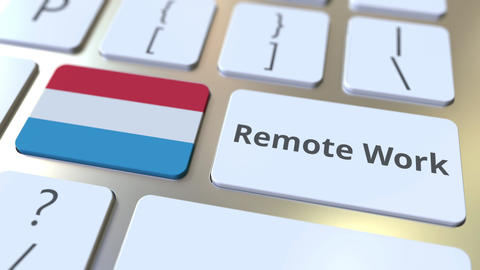 Remote Work text and flag of Luxembourg on the computer keyboard. Telecommuting ライブ動画