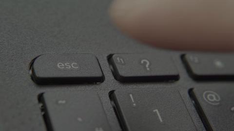 Finger presses Escape button on keyboard Live-Action