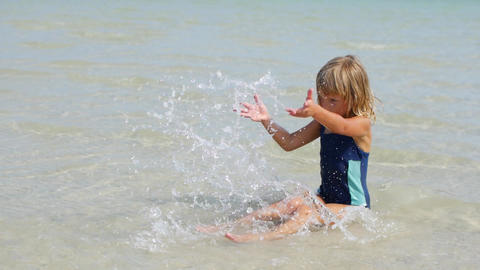 6-year-old girl sits in the sea in shallow water and splashes water Live Action