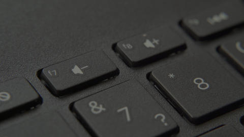 The finger presses the Mute button on the keyboard Live-Action