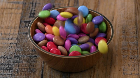 Slow motion, Colorful candies in a wooden bowl case isolated on wood background Live Action