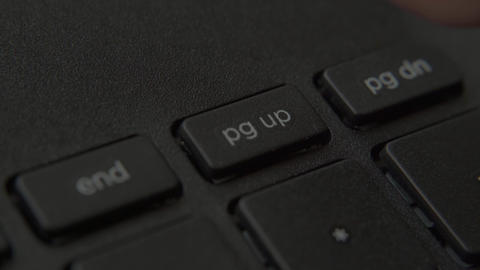 The finger presses the page up button on the keyboard Live-Action