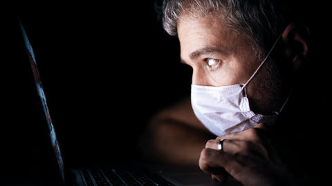 Worried man wearing face mask looks through a news site on his laptop. Latest Live-Action