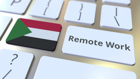 Remote Work text and flag of Sudan on the computer keyboard. Telecommuting or Live-Action