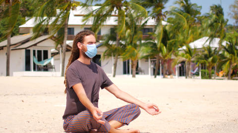 A masked young man meditates on the beach. Coronavirus epidemic Live-Action