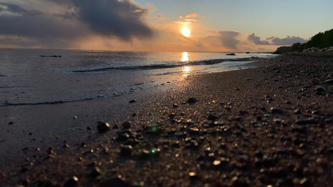The coast at sunset, the picturesque sunset, quiet water, a sandy beach, clouds Live Action